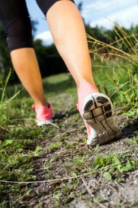 Walking or running legs in forest, adventure and exercising in summer nature